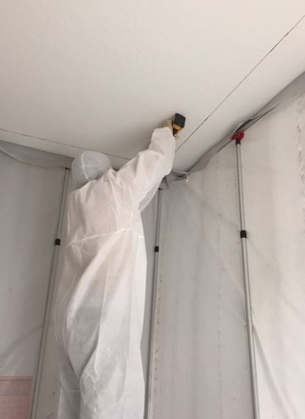 worker wearing protective gear attending to mold in ceiling
